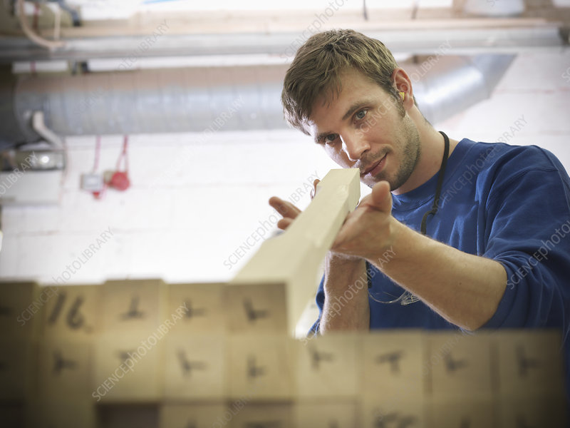 Worker examining wood in joinery