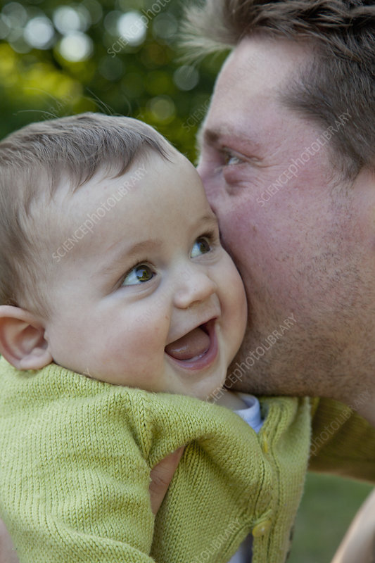 Father kissing laughing baby boy