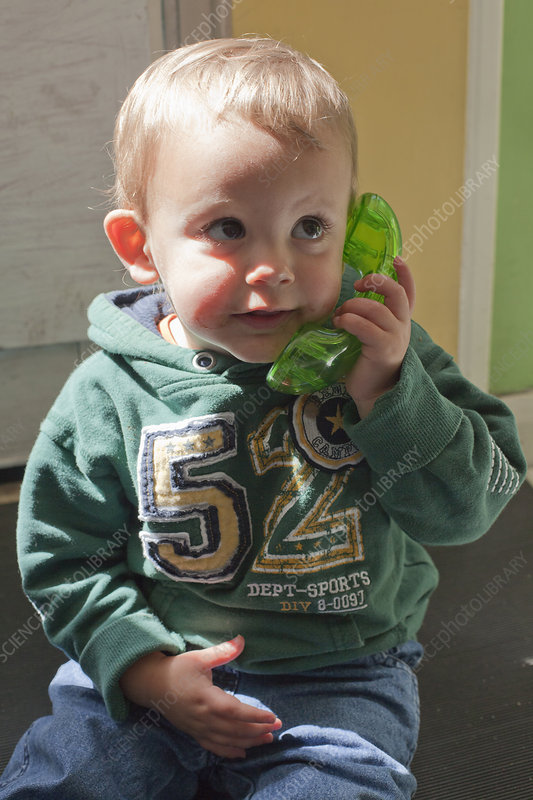 Baby boy playing with toy telephone