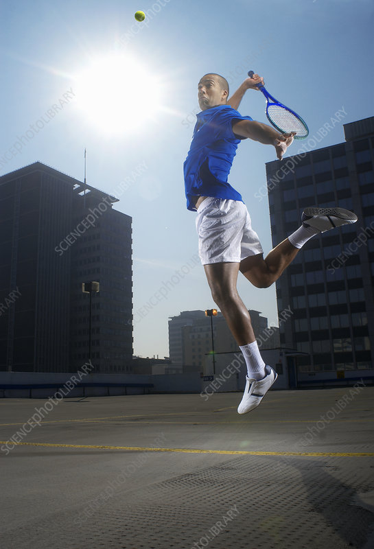 Tennis player jumping on rooftop court