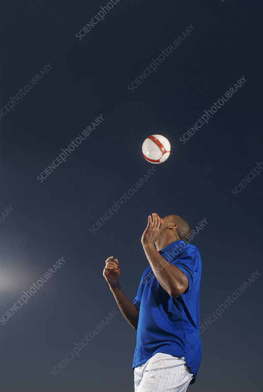 Man bouncing soccer ball on his head