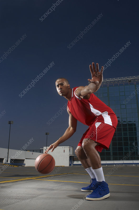 Basketball player dribbling on rooftop