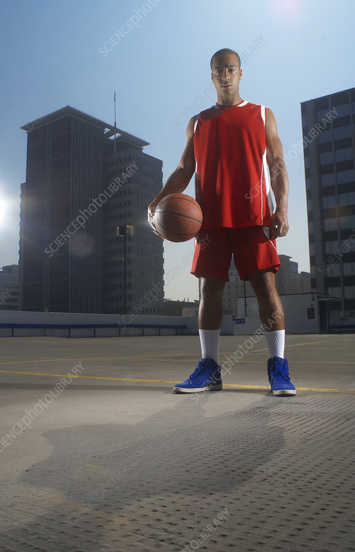 Basketball player with ball on rooftop