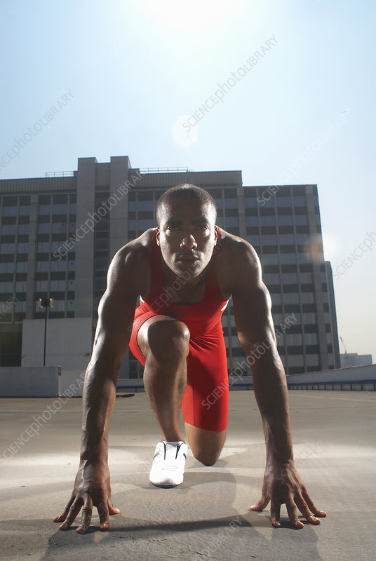 Runner in start position on rooftop