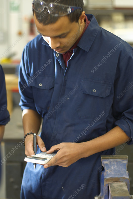 Worker using calculator in factory