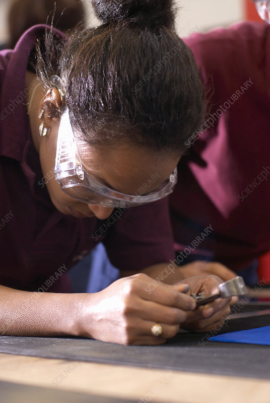 Worker using compass in factory