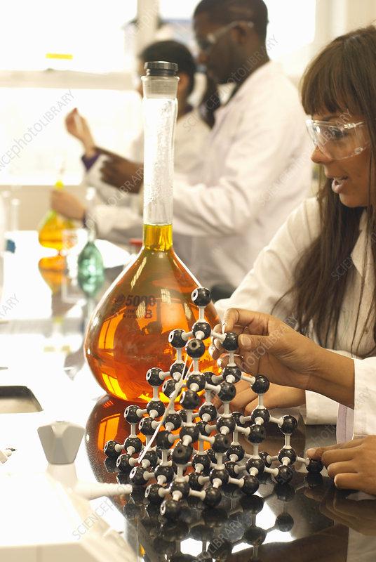 Scientist examining beaker in lab