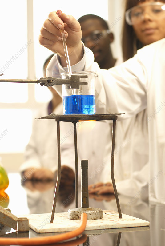 Scientist adding solution to beaker