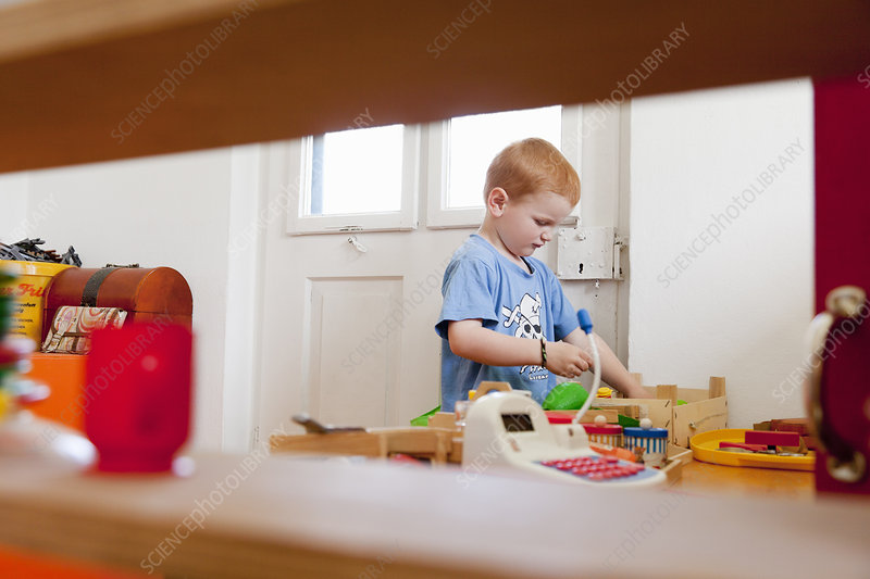 Boy playing with toys in living room
