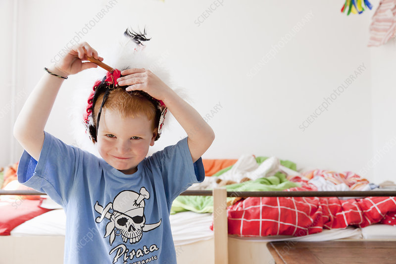 Boy playing with hat in bedroom