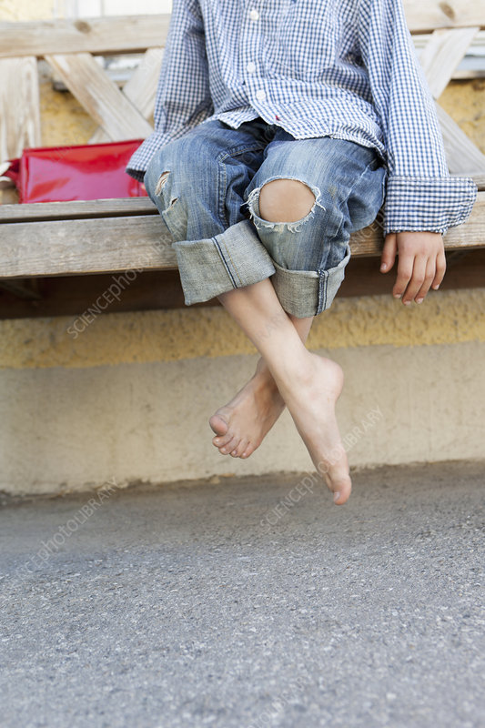 Close up of boy's bare feet on bench