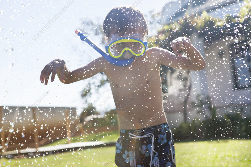 Boy in snorkel playing with hose