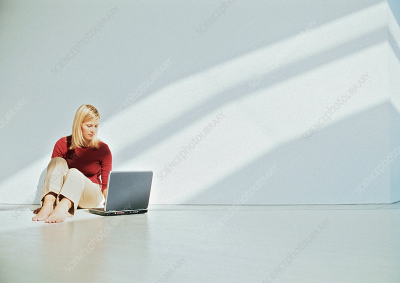 Businesswoman using laptop on floor