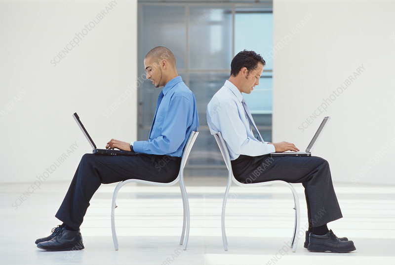Businessmen using laptops in lobby