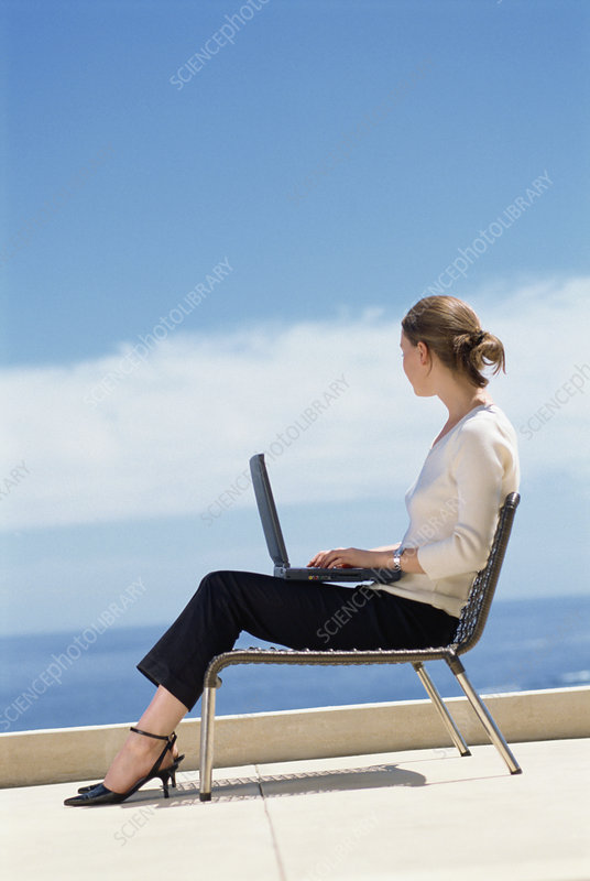 Businesswoman using laptop on roof