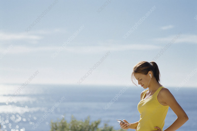 Woman listening to headphones outdoors