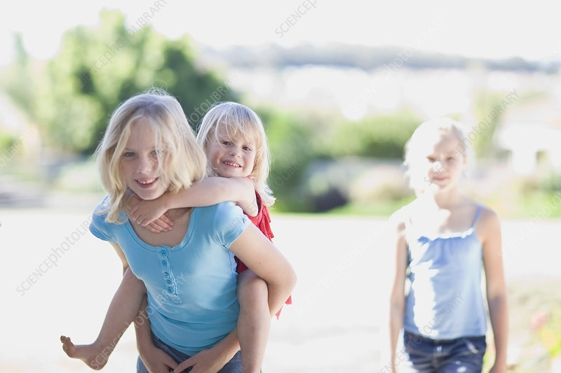 Girl carrying younger sister piggyback
