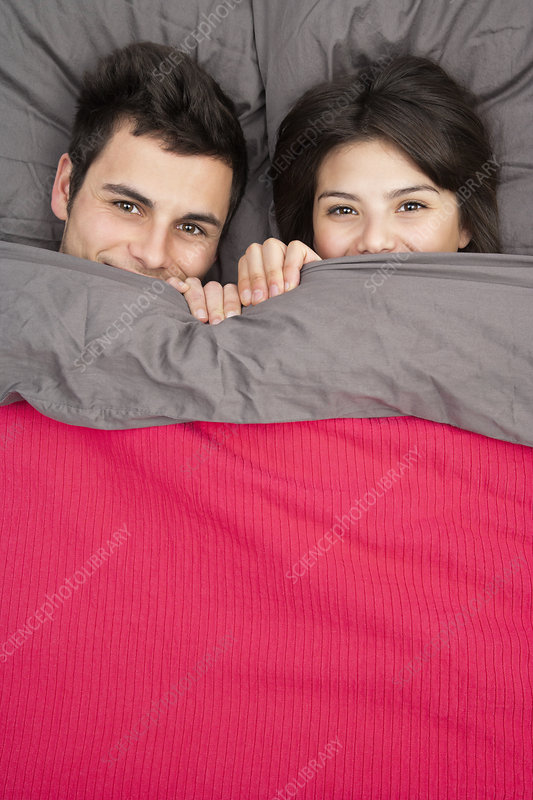 Couple peering out from under blanket