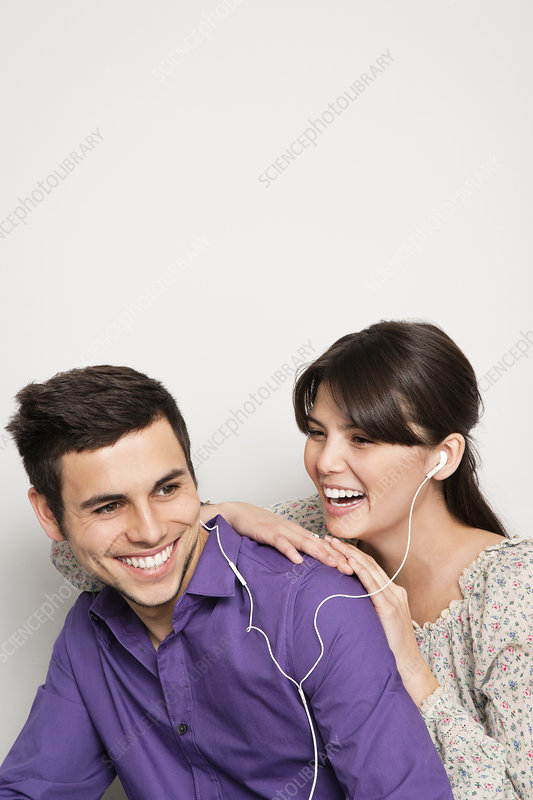 Smiling couple listening to headphones