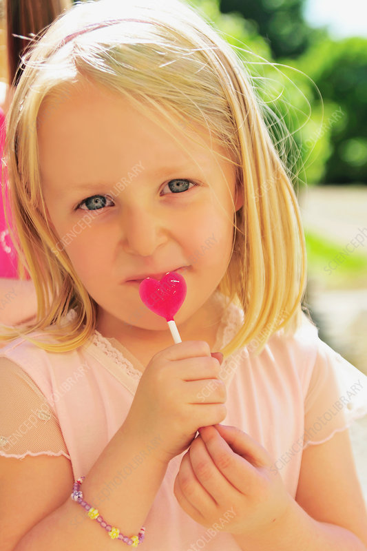 Girl eating heart-shaped lollipop