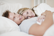 Smiling couple relaxing in bed