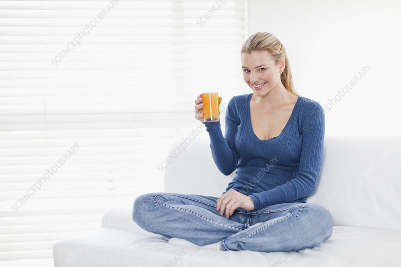 Woman drinking orange juice on couch