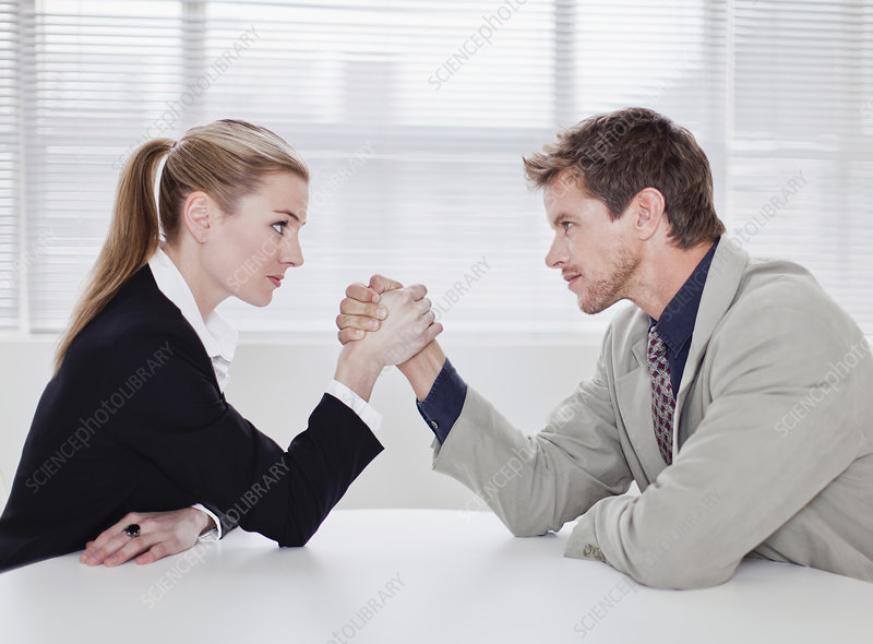 Rival business people arm wrestling