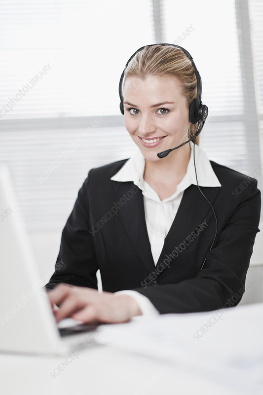 Businesswoman in headset using laptop