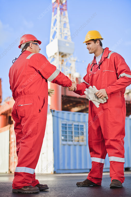 Workers shaking hands on oil rig