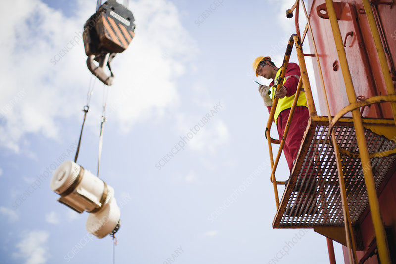 Worker directing crane on oil rig