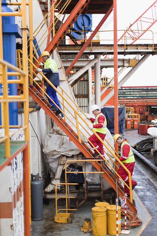 Workers climbing stairs on oil rig