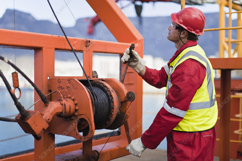 Worker spooling cord on oil rig