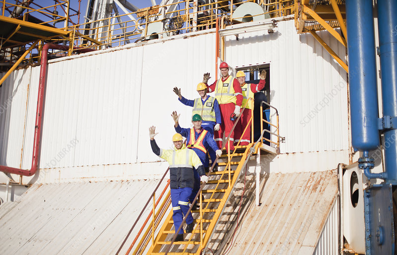 Workers waving from steps of oil rig