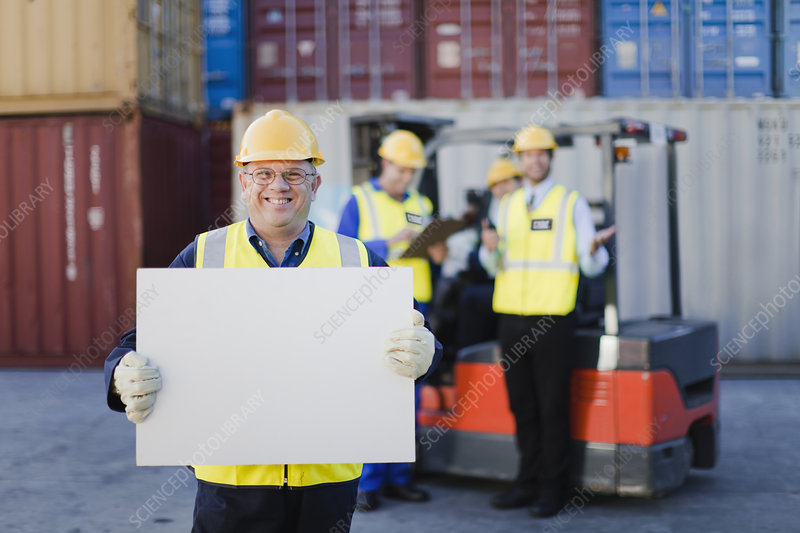 Worker holding sheet in shipping yard