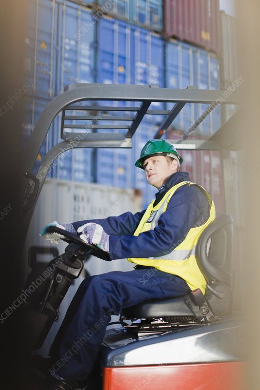 Worker using machinery in shipping yard