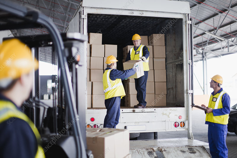 Workers unloading boxes from truck