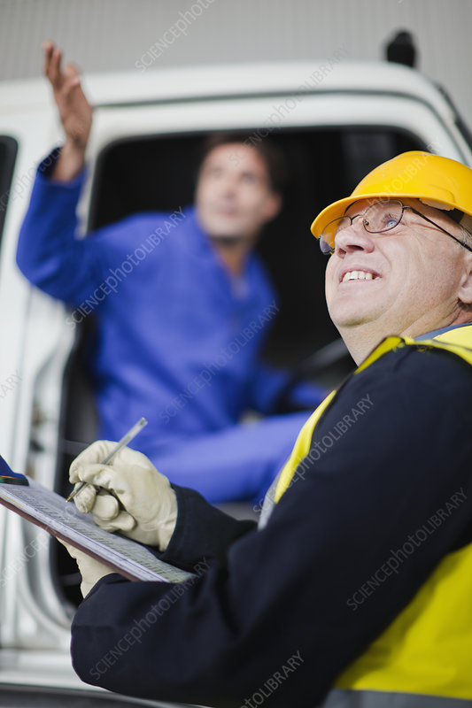 Truck driver talking to worker