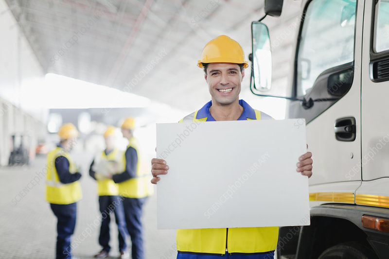 Worker holding blank card by truck
