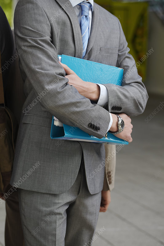 Businessman carrying folder in courtyard