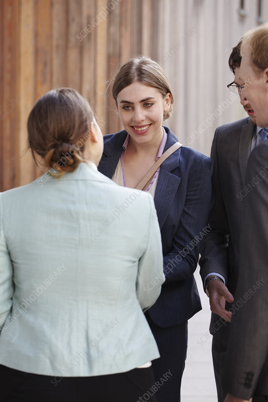 Businesswomen shaking hands in courtyard