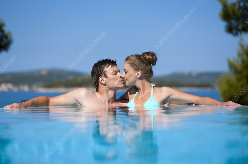 Couple kissing in infinity pool