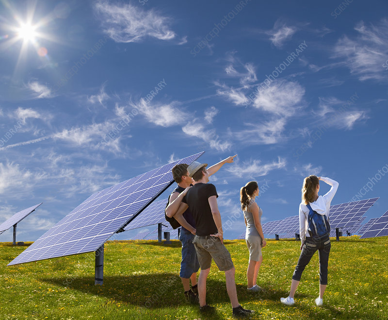 People standing in field by solar panels