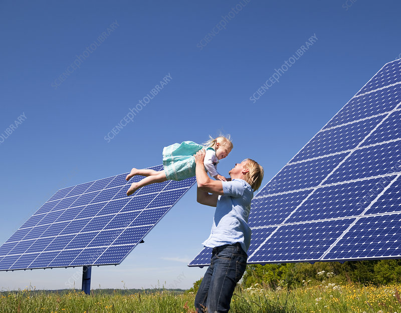 Father and daughter by solar panels