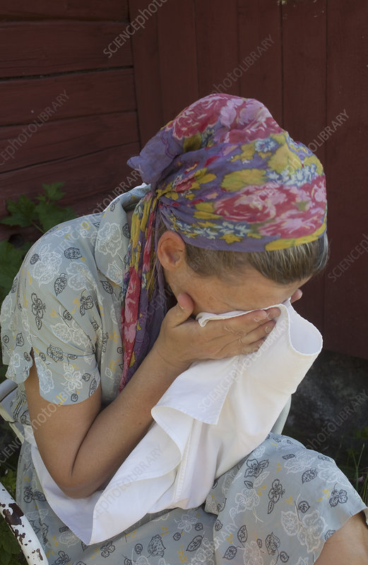 Woman wiping her face outdoors