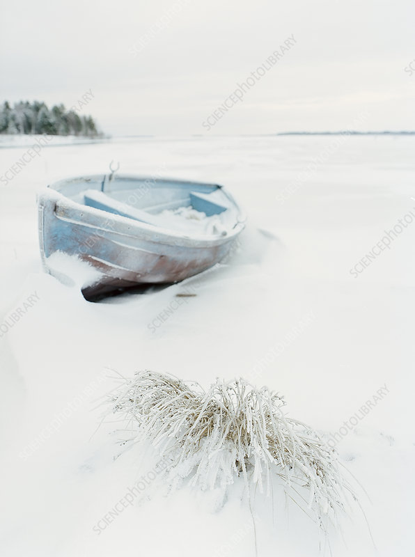 Boat in snow covered field