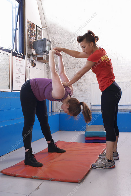 Woman stretching with trainer in gym