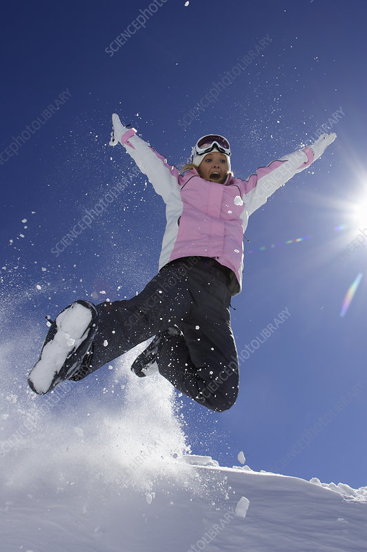 Woman in ski boots playing in snow