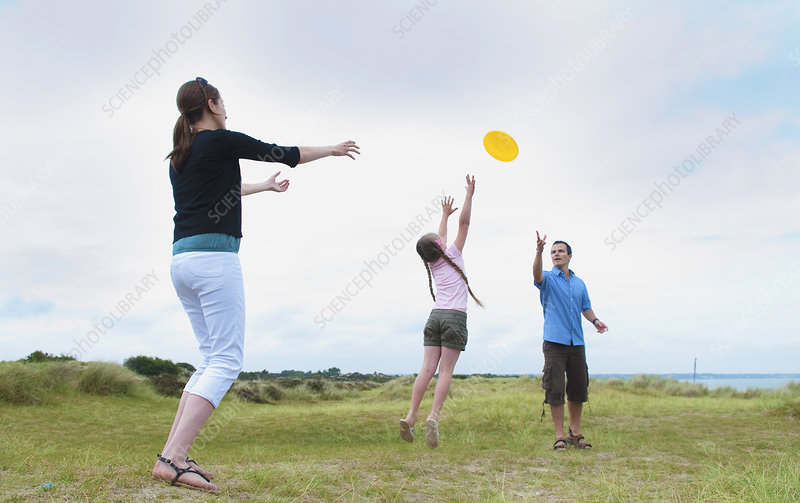 Family playing with frisbee outdoors