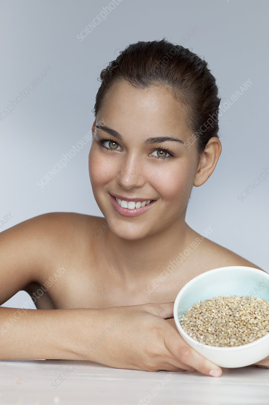 Smiling woman holding bowl of grains