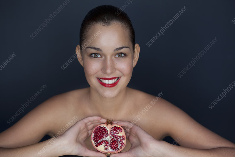 Woman holding halved pomegranate